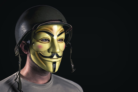 MILAN,ITALY, November, 2017: Hacker wear anonymus mask and usa army helmet in the dark Editorial