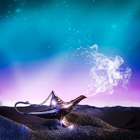 砂漠の古典的な真鍮アラジンランプと煙