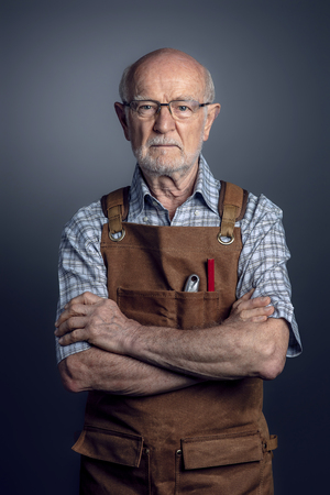 portrait of old carpenter with apron