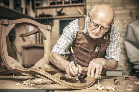 Ein älterer Zimmermann benutzt eine Bürste auf einem unfertigen Stuhl Standard-Bild