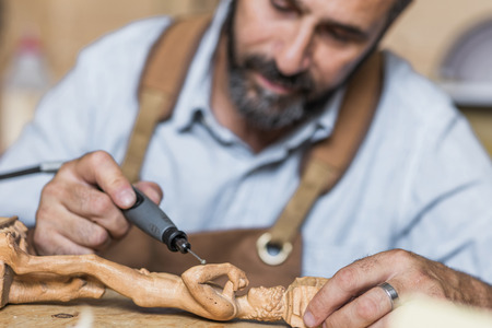 caucasian carpenter at work in a workshop use drill