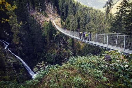 People on suspended bridge in Rabby valley, Italian alps Stock Photo