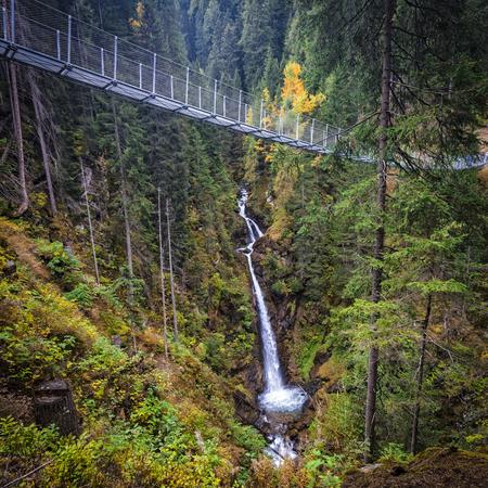 Waterfall under suspended bridge in Rabby valley on Italian alps