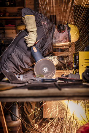portrait of manual worker with grinder in action