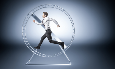 junger Geschäftsmann läuft in riesigem Hamsterrad