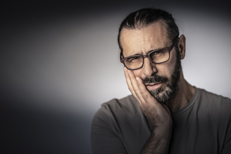 portrait of man with glasses and toothache Stock Photo