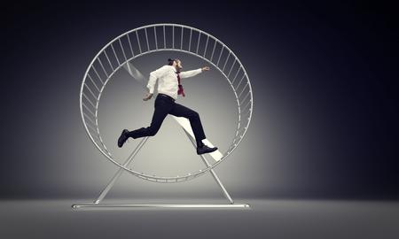 Kaukasischer Geschäftsmann läuft in abstraktem Hamsterrad Standard-Bild