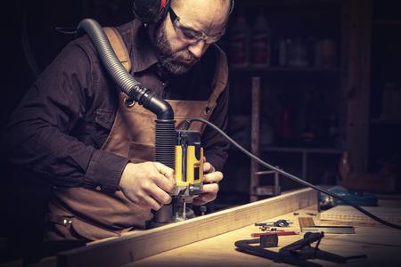portrait of carpenter using a vertical router