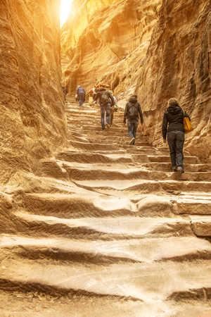 Travelers and tourists climb the impressive staircase carved into the rock that leads to the monastery of Petra. Jordan.