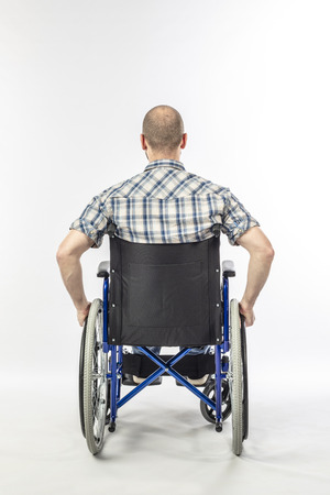 Man sitting on a wheelchair because he is injured. white background and back view. Concept of disability and medical support. Imagens