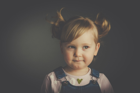 Studio portrait of a 2 year old girl with pigtail hair. Vintage style.