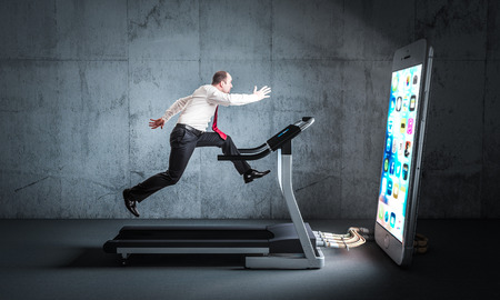 Businessman runs on a treadmill to feed a huge smartphone. Concept of technology addiction.