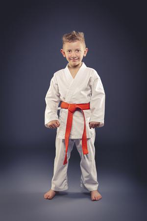portrait of a smiling child with kimono practicing martial arts, orange belt