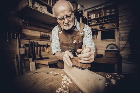 old carpenter with glasses smooths a piece of wood with the hand plane inside his workshop
