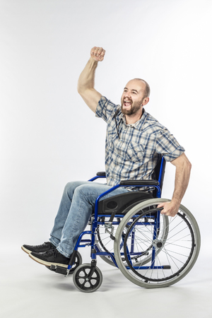 Disabled man on wheelchair with arm raised as a sign of victory. Concept of challenge and positivity. Banque d'images - 124479634