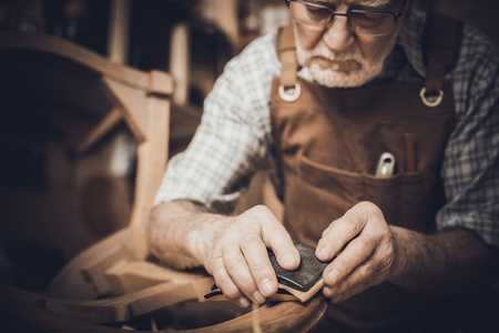 Elderly carpenter with glasses smooths an unfinished chair. workShop in the background. Stok Fotoğraf