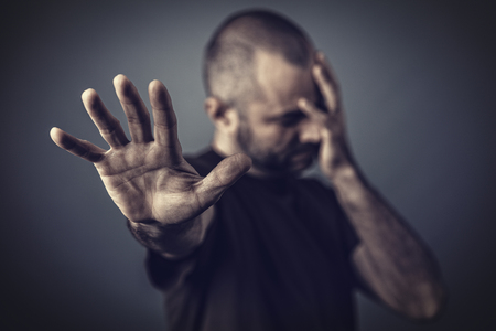 Desperate man with hand on his face and another hand leaning forward to protect himself.