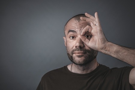 Portrait of a man looking through his fingers positioned to form a circle around his eye.
