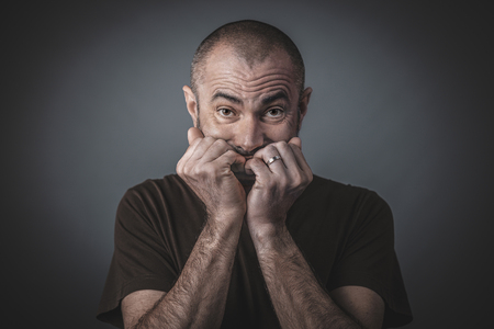 Portrait d'un homme effrayé avec les mains fermées jointes près de la bouche. Cheveux et barbe courts, vêtements décontractés.