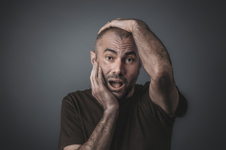 Portrait of a man holding his head with both hands with a surprised expression. Stok Fotoğraf
