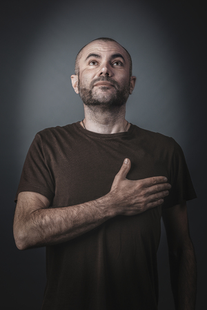 Satisfied and proud man posing with his hand over his heart. Studio portrait. Imagens