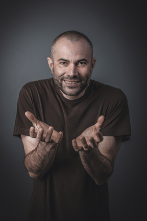 Portrait of a man with satisfied expression and clasped hands in front of him. Look towards the camera. Stok Fotoğraf