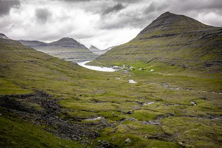 Landscape nature on the Faroe Islands, village near a lake.