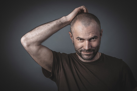 Portrait of a man scratching his head with a thoughtful expression. Direct look at the camera. Casual clothes studio shot image.