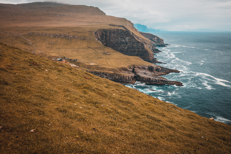 View of the cliffs and the village on the island of Mykines, Faroe.