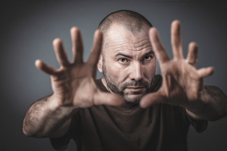 Studio portrait of Caucasian man with open hands and arms outstretched forward. Selective focus on the face.