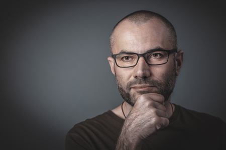 Portrait of man with glasses and hand on chin. Thoughtful look. Caucasian with short hair, studio shot.