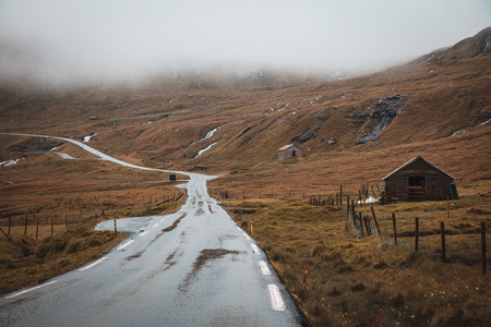 Image of travel on a lonely road in the Faroe Islands. Mountains and traditional houses.