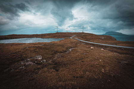 Windmills on the hills of the Faroe Islands. Sheep in the foreground and ocean in the background.