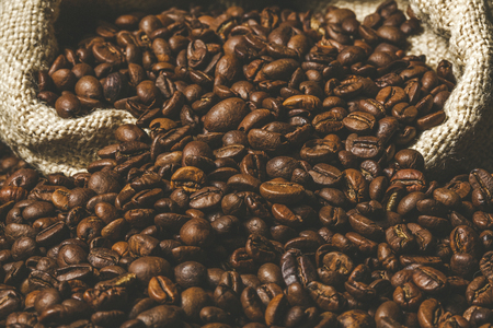 Detail of roasted coffee beans coming out of a jute sack. Stok Fotoğraf