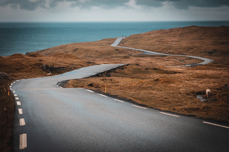 Winding road in the middle of the Faroe Islands. Ocean in the background. Stok Fotoğraf