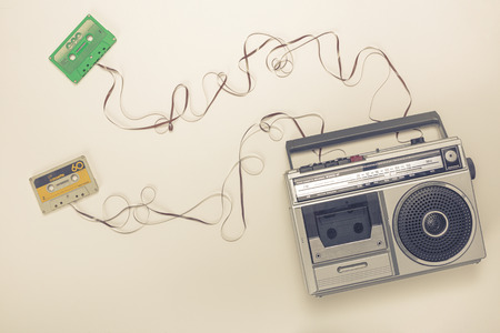 Old radio with tape recorder and cassettes with ribbon forming a wire. Flat lay style.