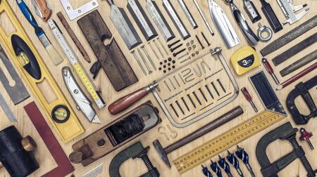 View of a set of carpenters tools on a wooden background. Style flat lay.