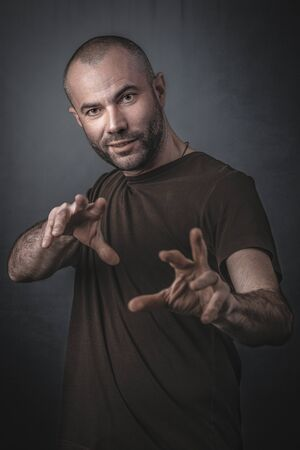 portrait of man with hands outstretched forward in magic gesture.Studio Shot Foto de archivo