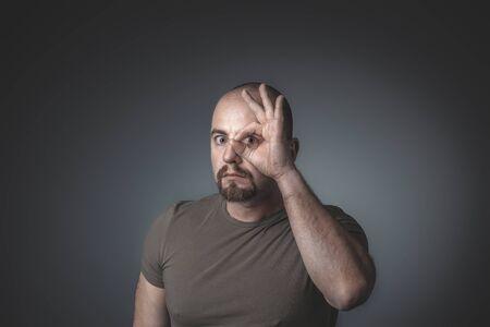 Caucasian man looks through his fingers closed in a circle. studio shot