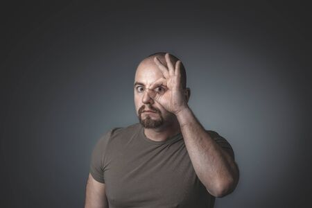 El hombre caucásico mira a través de sus dedos cerrados en círculo. tiro del estudio