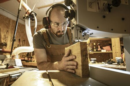 portrait of a carpenter inside his carpentry workshop using a band saw. Wear ear and eye protection Stock Photo