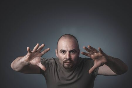 portrait of a man with a determined and intense expression, hands in front of him and open, studio shot.
