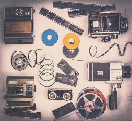 composition of different types of cameras, film and snapshots, film camera and slide viewer, several films present on stage.