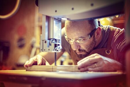 detail of a carpenter at work cutting a plank with a band saw in his workshop, Caucasian with a beard and protective glasses.