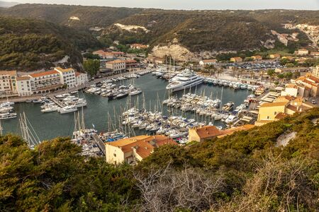 view of the historic city of Bonifacio in Corsica, harbor with boats. Mediterranean France.