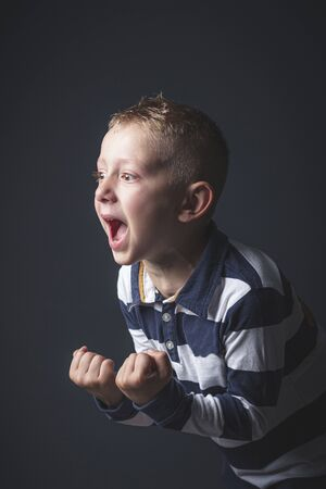 studio portrait of a 6 year old kid caucasian boy screaming in despair.
