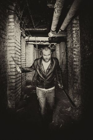 portrait of a serial killer holding knives and running inside an underground tunnel. Stok Fotoğraf