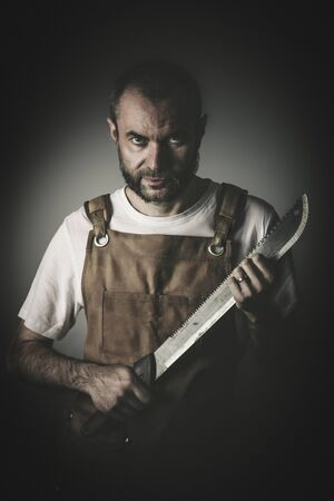 dramatic portrait of a killer holding a machete, concept of danger and image suitable for the horror theme. Stok Fotoğraf