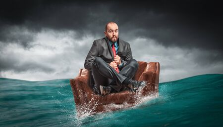 man sitting on an armchair floating on the water of the ocean. concept of crises and problems at work. Reklamní fotografie