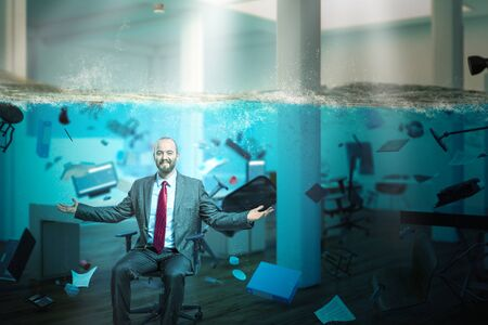 smiling businessman sitting in an office completely flooded with objects floating in the water. concept of problems at work and positive vision.